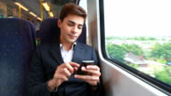 HD:Young businessman playing mobile phone on the train.