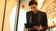 HD: junger Geschäftsmann spielen tablet im Zug.