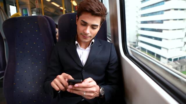 HD: junger Geschäftsmann mit Handy auf dem Zug.