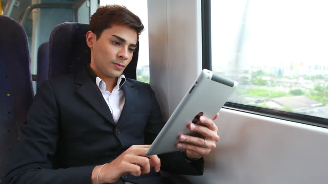 HD:Young businessman using tablet on the train.