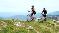 HD:Young couple reaching the mountain peak