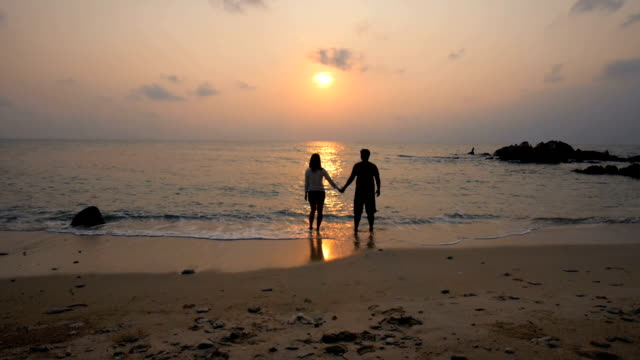 HD:Young Couple Walking on Beach to the sea holding hands at sunset time ,slow motion ,relaxation concept