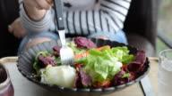 HD: giovane donna mangiare Insalata con panna souce