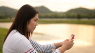 HD:Young woman touching smartphone in nature