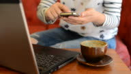 HD:Young woman typing smartphone in coffee cafe