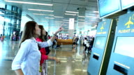 HD:Young women looking at schedule display in the airport.