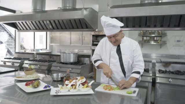 Männlichen Chefkoch Gemüse Hacken, die Gerichte zu beenden