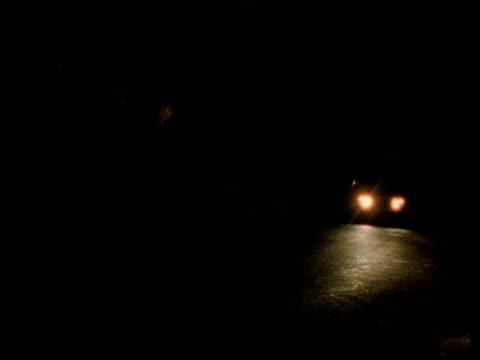 Headlights of jeep travelling along dark road pass camera