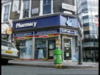 Prescription Charges to Go Up **** FOR ENGLAND Central London Exterior of chemist shop woman customer inside chemist shop as pharmacist takes her...