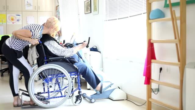 Hälsoarbetare bistå Senior Kvinna i sjukgymnastik motion