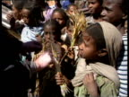 Healthy Ethiopian children show Bob Geldof crops that they've grown since famine of 1984 Ethiopia; Dec 87