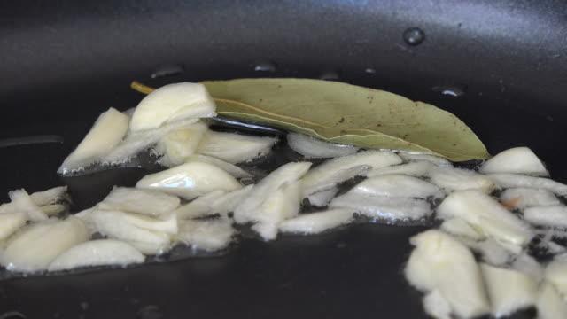Healthy food ingredients, fresh garlic and bay leaf cooking in hot vegetable oil.