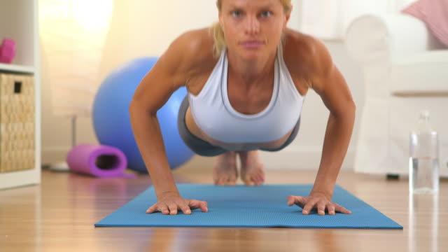 Healthy woman doing push ups and looking at camera