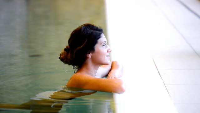 Healthy woman swimming in pool and relaxes with hot tub