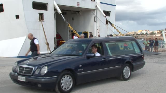 Hearses and lorries carrying hundreds of coffins arrive on Lampedusa ahead of a ceremony to honour the 300 asylum seekers feared dead after the boat...