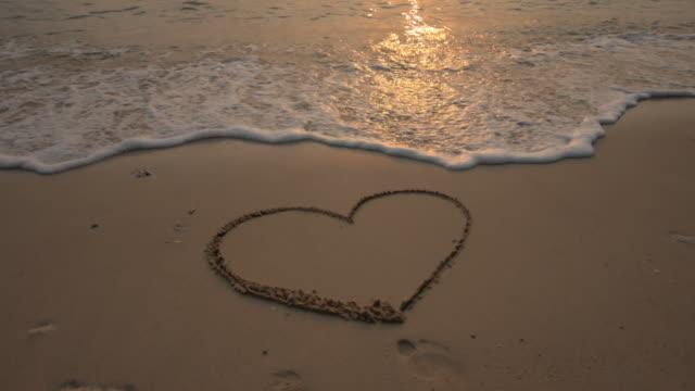Cuore forma sulla spiaggia di sabbia con l'onda gomma, 4 k (UHD