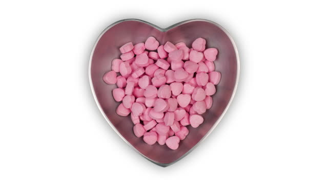 A heart-shaped silver dish filling with pink candy hearts and emptying again, time lapse