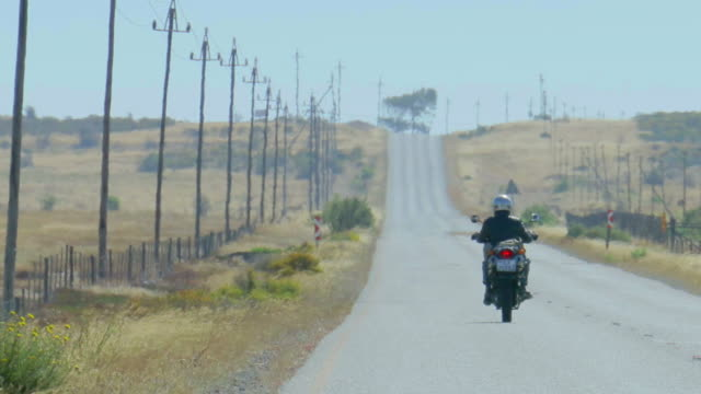 Heat haze on road and biker driving into distance/ Western Cape/ South Africa