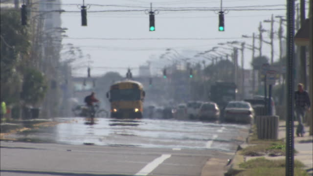 Heat waves distort a school bus and other vehicles on a busy street.
