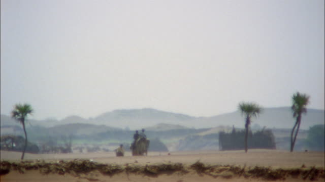 Heat waves shimmer over a desert as riders travel on camels.