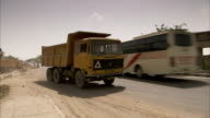 A heavy dump truck moves around traffic near the construction of the road to Jaipur, India. Available in HD.