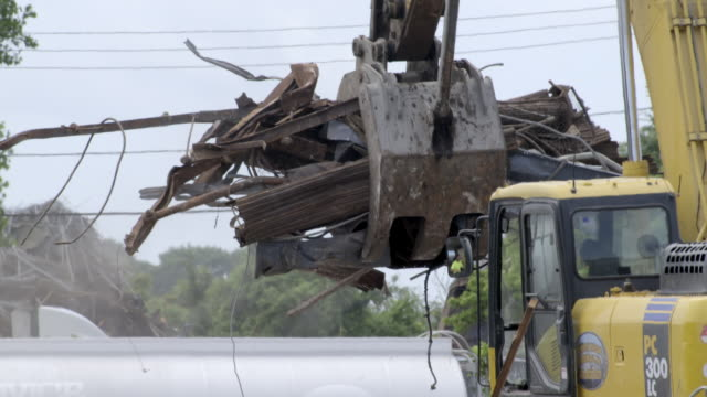 Heavy equipment trucks and tractors move and sort scrap pile debris for recycling in junk yard. - 6