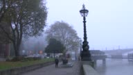 River Thames and Houses of Parliament ENGLAND London Westminster People along embankment by River Thames in foggy conditions / boats on River Thames...