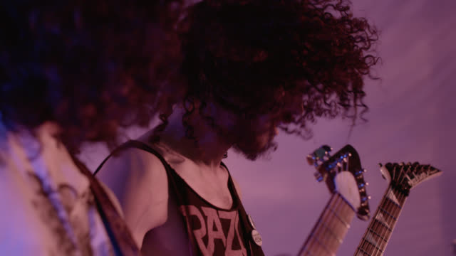 Heavy metal band play guitars and bang their heads in unison in slow motion