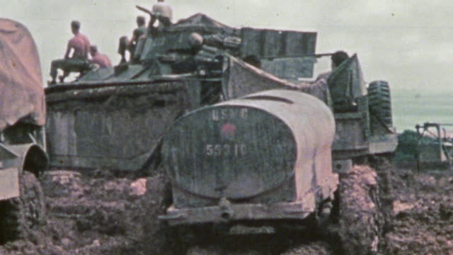 Heavy mud weighing down vehicles Jeeps M35 trucks and towed trailers / Okinawa Japan