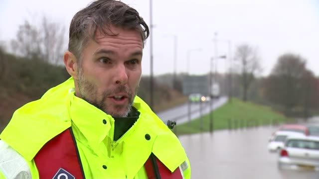 Heavy rain across UK causes flooding and travel disruption Chris Francis interview SOT Traffic along street and worker trying to clear drain Traffic...