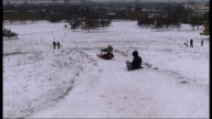 Primrose Hill general views Dog running across snow and sitting down in front of owner / back view of people sledging down hill / two men carrying...