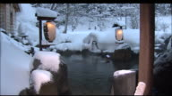 Heavy snow covers open-air hot springs illuminated by paper lanterns