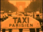 Heavy traffic on Champs Elysees in Paris / taxi sign in foreground