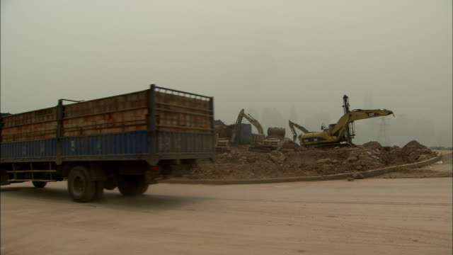 A heavy truck approaches a construction site. Available in HD.