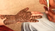 Heena mehndi artist making a design on woman hand