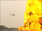 Helicopter flies behind raging oil well fire in desert Kuwait 31 Mar 03
