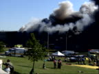 Helicopter flies into billow of smoke / rescue workers organize / Rescue vehicles drive away