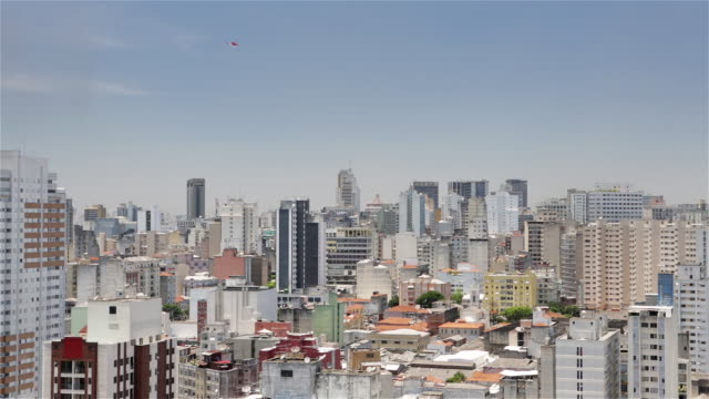 MS, HA A helicopter flies over downtown Sao Paulo skyline / Sao Paulo, Brazil