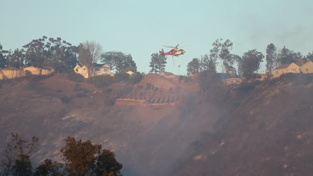A helicopter flies over the Bel Air neighborhood of Los Angeles during the Skirball fire