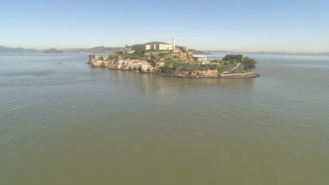 A helicopter flies over the island of Alcatraz.