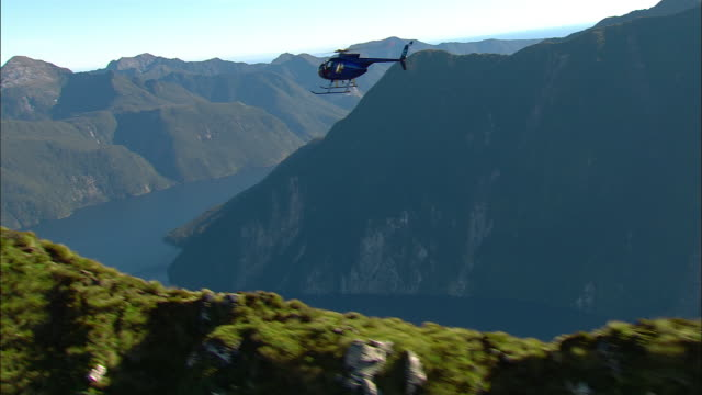 AIR TO AIR, Helicopter flying above mountain river, Fiordland National Park, New Zealand