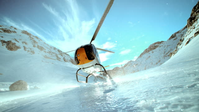 SLO MO LD helicopter landing on icy surface of mountain