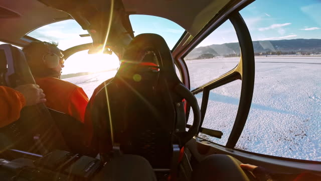 POV helicopter passenger looking at pilot flying over snowy landscape