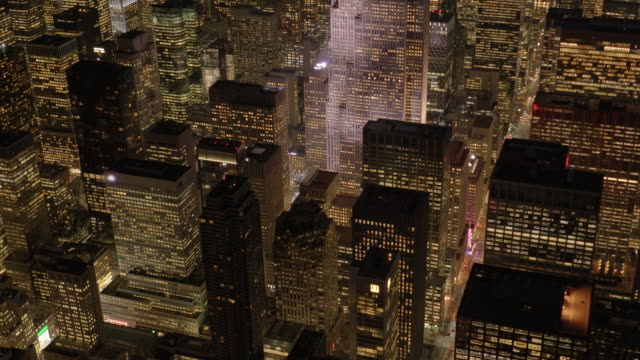 helicopter shot of new york city at night overlooking skyscraper buildings