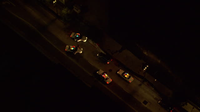 TS Helicopter spotlighting a stopped vehicle surrounded by police cars and officers on foot on a city street