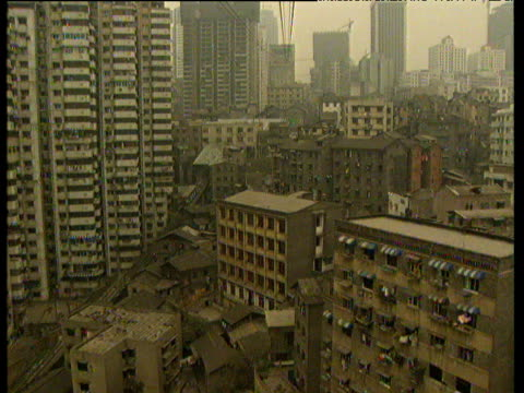 Helicopter tracks forwards though densely packed industrial city. Dirty coloured tall shabby skyscrapers and other industrial buildings are piled high next to each other Chongquing China