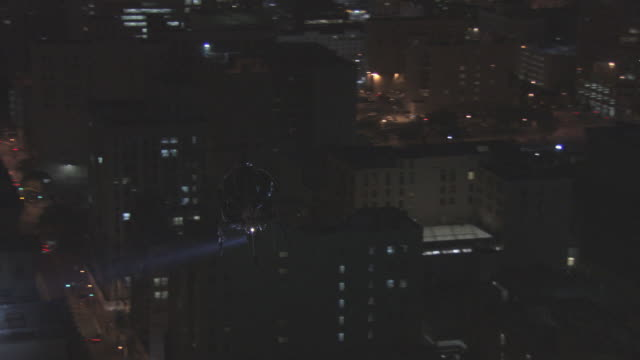 AERIAL Helicopter with search light scanning buildings in city / United States