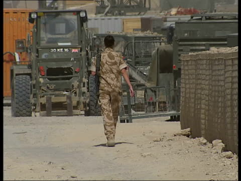 Camp Bastion general views AFGHANISTAN Helmand Province Camp Bastion EXT Female British soldier walking towards at Camp Bastion / Soldier along by...