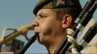 Helmand Province EXT Bagpiper plays lament at Armistice Day service as soldiers from the Argyll and Sutherland Highlanders 5th Battalion The Royal...