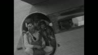 Helmeted men quickly don parachutes and walk to airplane marked 'U S Navy' / the men peer through open door of plane / their biplane takes off / VS...